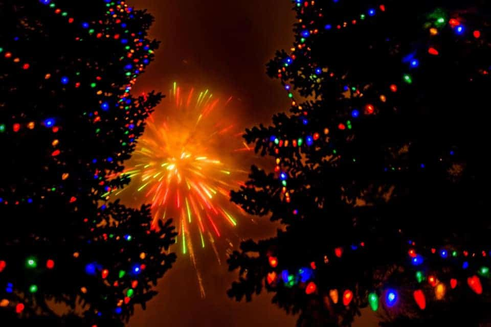 Fireworks through lighted Christmas Trees